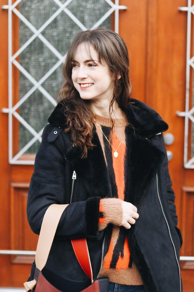 Winteroutfit kaufen Strickpullover schwarze Felljacke kombinieren streetstyle